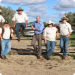 Cattle producers leaning against fence on a farm