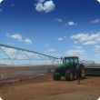 Tractor and seeder next to centre pivot irrigator in the Pilbara.