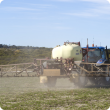 Boom spray applying chemical over pasture paddock