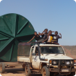 Aboriginal children sitting on the back of a ute which is towing a large water tank
