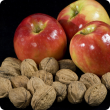 Three red apples and walnuts.