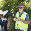 DAFWA contract staff Elisabeth Dinter (with spray pack) and Laura Berry (clip board) with DAFWA quarantine officer Chris Brandis baiting for Qfly in the Alfred Cove area.