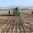 View of the back of the cone seeder as the first trial plot is seeded of the 2012 trial program.  One staff member is on the seeder while others are confirming all equipment is working properly