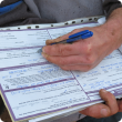 Photo of a person completing a sheep NVD form.